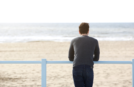 Portrait from behind of a young man standing alone looking at the sea Stock Photo