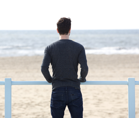 Portrait of a young man standing outdoors looking at the sea Imagens