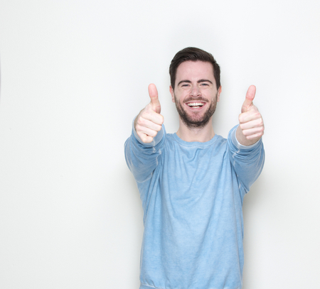 Portrait of a young man smiling with thumbs up sign Stock Photo