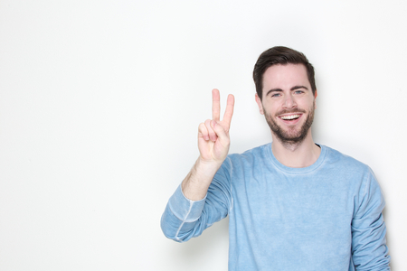 Portrait of a young man smiling with victory sign on white background