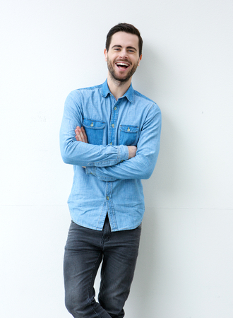cool attitude: Portrait of a happy young man laughing with arms crossed