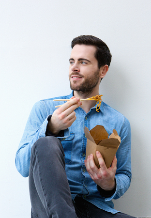 man looking out: Portrait of a cool guy eating chinese take away food Stock Photo