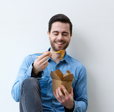 Close up portrait of a happy young man eating asian food with chopsticks