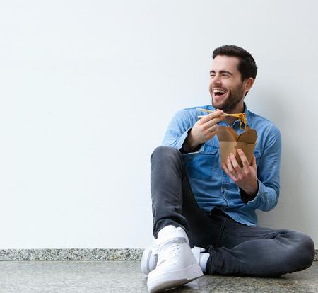 Retrato de un hombre joven y atractiva de comer comida china con palillos Foto de archivo - 30016500