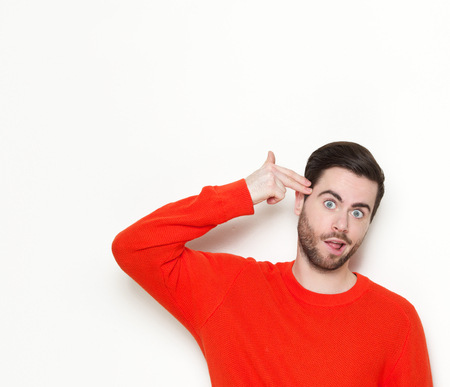 Portrait of a funny young man pointing finger gun gesture to head photo