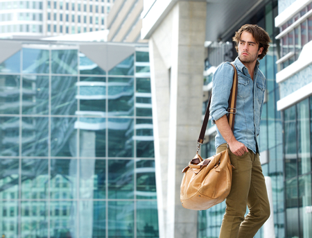 Portrait of a handsome young man walking outdoors with bag photo