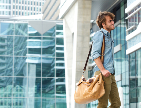 Portrait of a fashionable young man smiling with travel bag outdoors photo