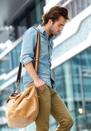 Portrait of a stylish young man walking in the city with travel bag photo