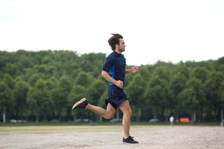 Completo vista lateral del cuerpo de un joven Atlético correr al aire libre