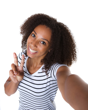 happy african woman: Self portrait of a happy young woman making selfie against isolated white background Stock Photo