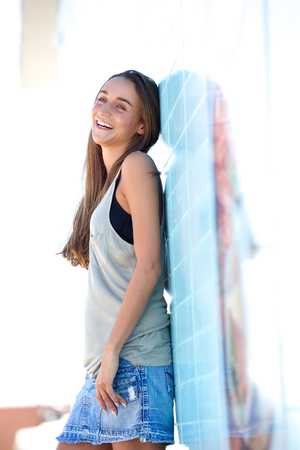 denim skirt: Profile portrait of a smiling young woman standing outside