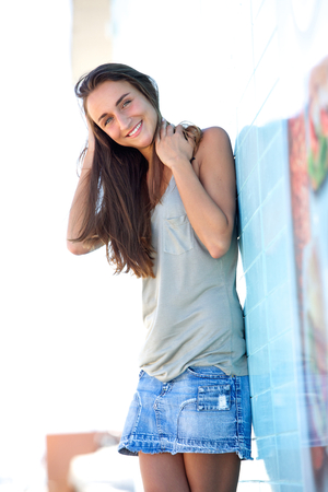 denim skirt: Portrait of a cute young woman smiling outside