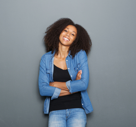 black woman face: Portrait of a smiling young woman posing with arms crossed on gray background