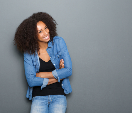 smiles: Portrait of a happy young african american woman posing with arms crossed Stock Photo
