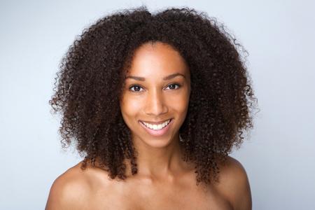 mujeres negras desnudas: Close up retrato de una hermosa mujer afroamericana sonriente sobre fondo gris