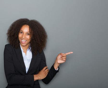 Close-up portret van een lachende zakelijke vrouw wijzende vinger weergegeven: kopie ruimte