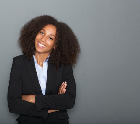 Close up retrato de una joven mujer de negocios sonriente con los brazos cruzados sobre fondo gris