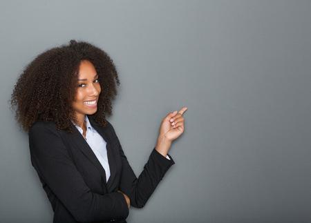 Közelről portré egy barátságos üzletasszony mutató ujját a szürke háttér