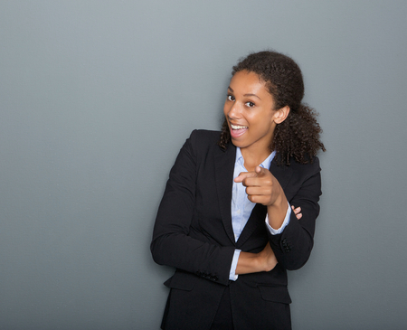 Close up portrait of a happy young business woman pointing finger at you photo