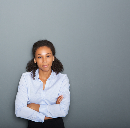 Close up portrait of a female business person with arms crossed on gray background