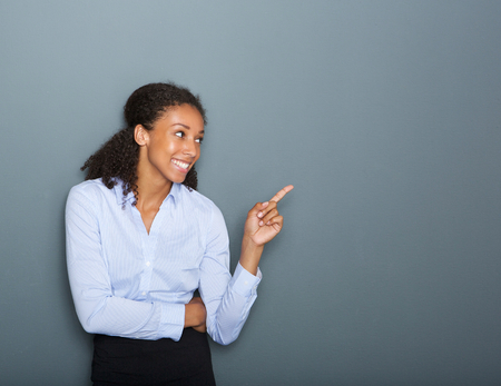 thinking woman: Close up portrait of a happy business woman pointing finger on gray background