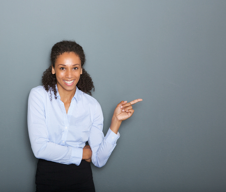 african business: Close up portrait of a confident business woman pointing finger on gray background Stock Photo