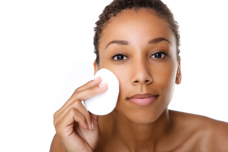 removing make up: Close up portrait of a beautiful black woman removing make up