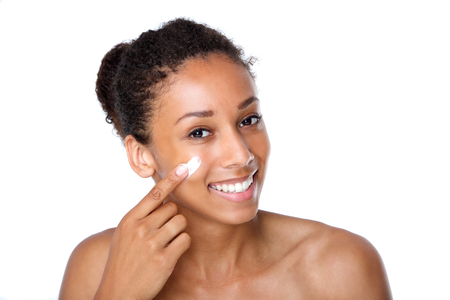 girl care: Close up portrait of an attractive young woman applying cream on face Stock Photo