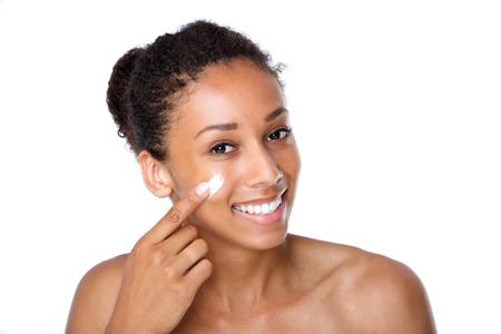 mujer maquillandose: Close up retrato de una mujer joven y atractiva la aplicaci�n de crema en la cara Foto de archivo