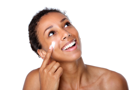 Close up portrait of a smiling woman applying lotion on face