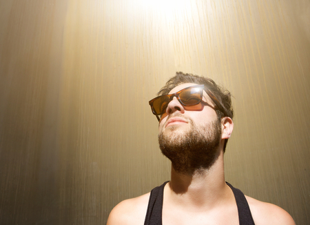 Close up portrait of a cool guy posing with sunglasses photo