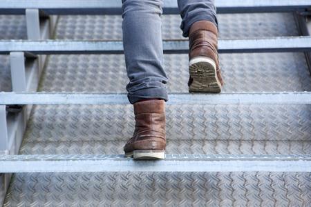 pies masculinos: Cierre de vista trasera del hombre subir escaleras en las botas Foto de archivo
