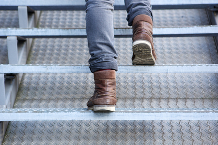 foot step: Close up rear view of man walking up stairs in boots