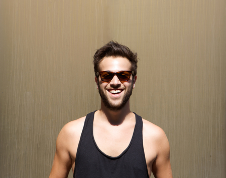macho man: Close up portrait of a handsome young man smiling with sunglasses
