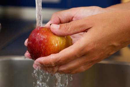 ingredients tap: Close up female hands holding apple under water Stock Photo