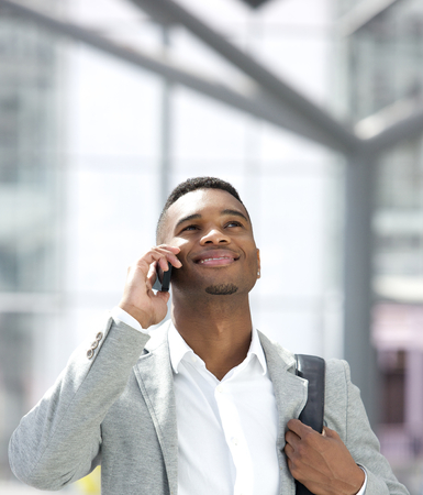 Close up portrait of a young african american man smiling with mobile phone photo
