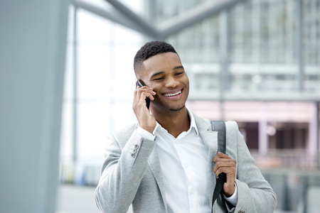 Close up portrait of a handsome young black man smiling with cellphone photo