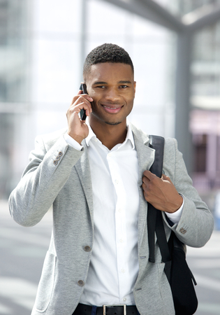 Portrait of a young black man with bag talking on mobile phone  photo