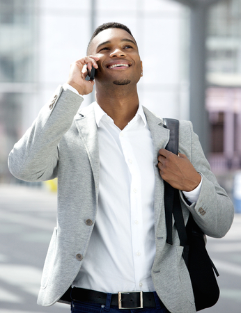 Portrait of a handsome young man walking and talking on mobile phone photo