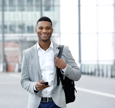Portrait of a handsome young man text messaging on mobile phone photo