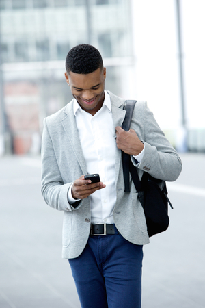 Portrait of a young man walking and looking at mobile phone photo
