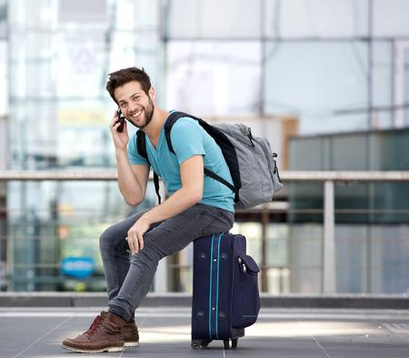Retrato de un hombre joven hermoso que se sienta en la maleta y que llama por el teléfono móvil en el aeropuerto