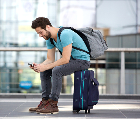 Portrait of a young male traveler sitting on suitcase and sending text message 版權商用圖片 - 31074134