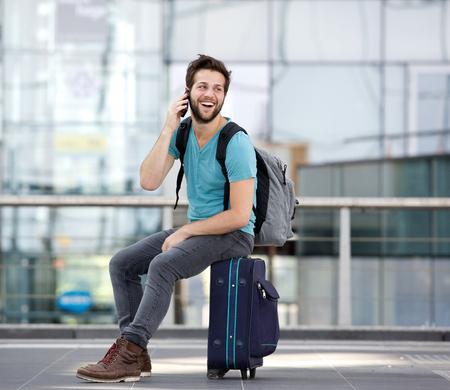 mochila viaje: Retrato de un hombre joven feliz llamando por tel�fono m�vil en el aeropuerto