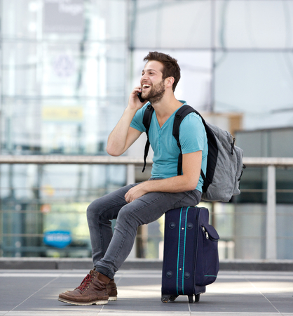 Portrait of a young man relaxing at airport and talking on mobile phone Stock Photo