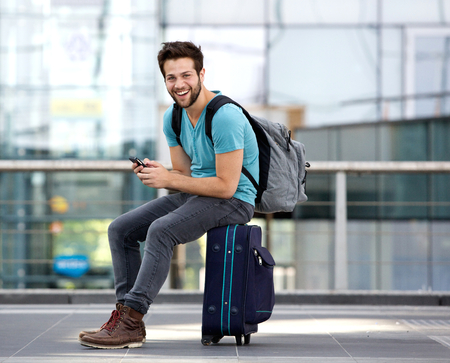Portrait of a young man sitting on suitcase and sending text message 版權商用圖片 - 31074141