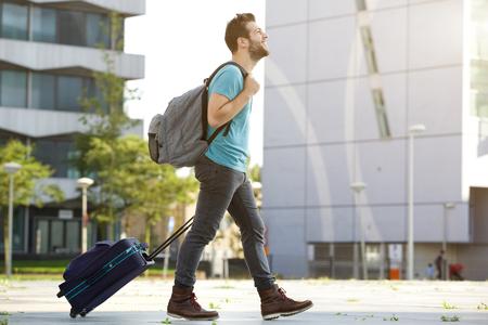 Profiel portret van een jonge man lopen met een koffer en tas