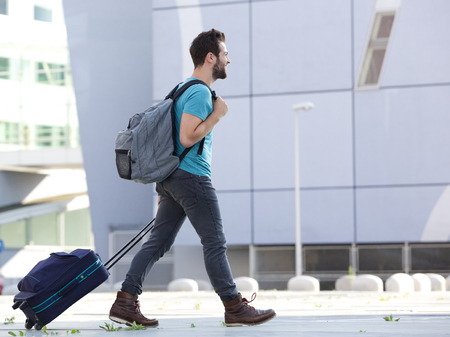 people walking white background: Profile portrait of a young man walking outdoors with suitcase Stock Photo