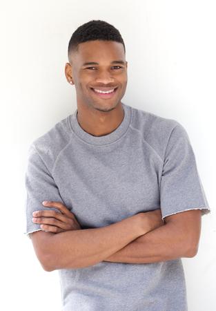 modelos hombres: Retrato de un joven hombre negro fresco sonriente con los brazos cruzados sobre fondo blanco