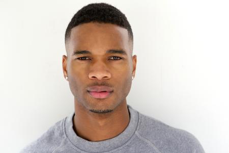 Close-up portret van koele jonge kerel poseren tegen een witte achtergrond